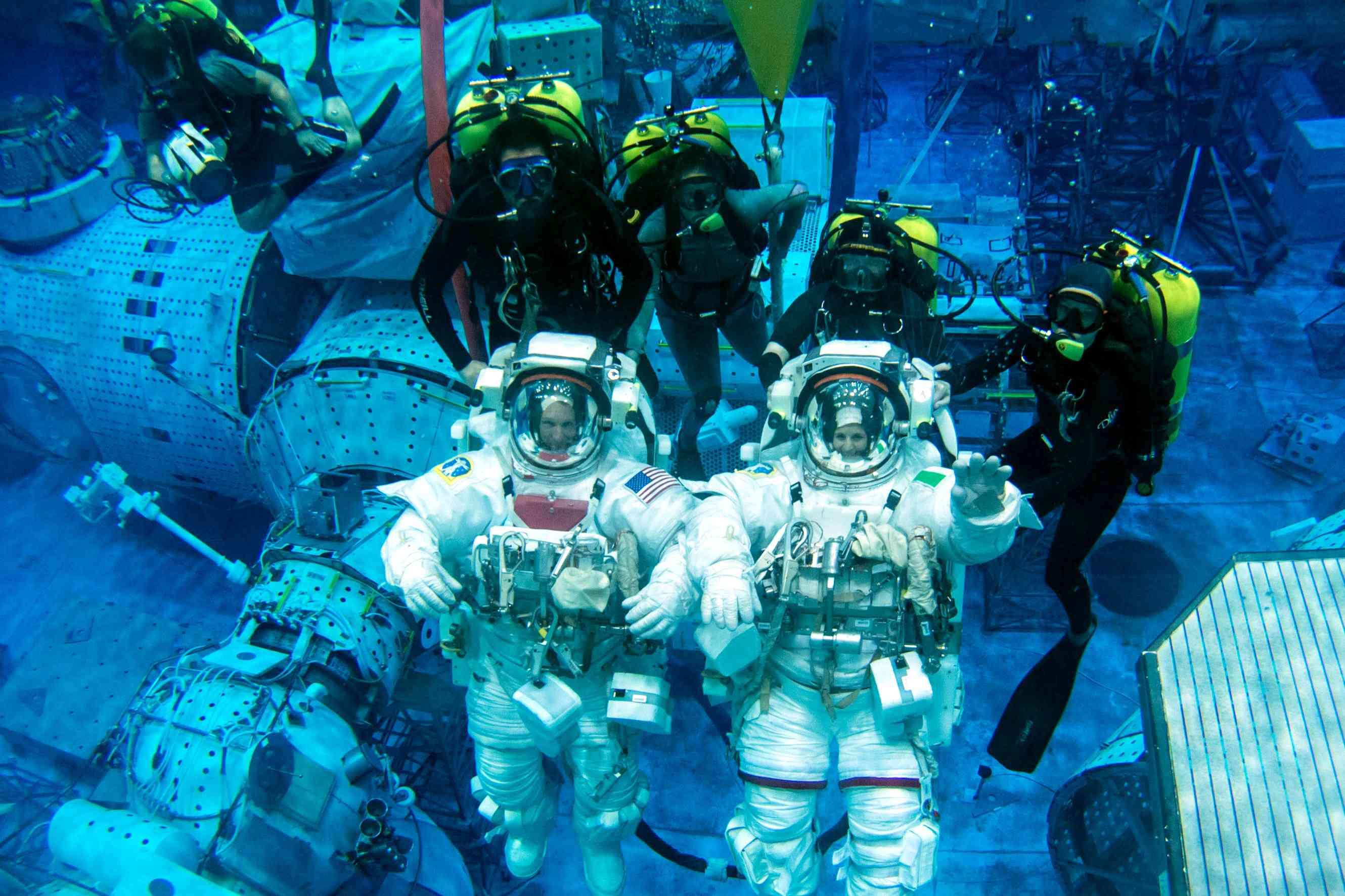 Astronauts train extensively underwater on Earth, wearing pressure suits, to simulate working in space