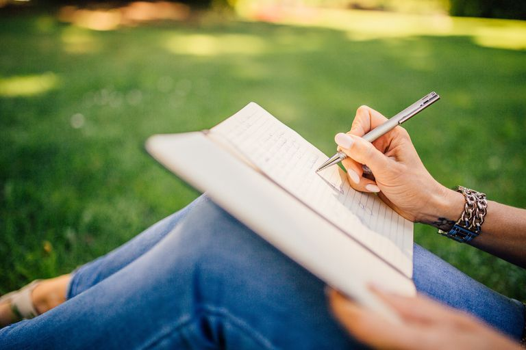 Person writing in a notebook while sitting outside, close up photo of notebook.