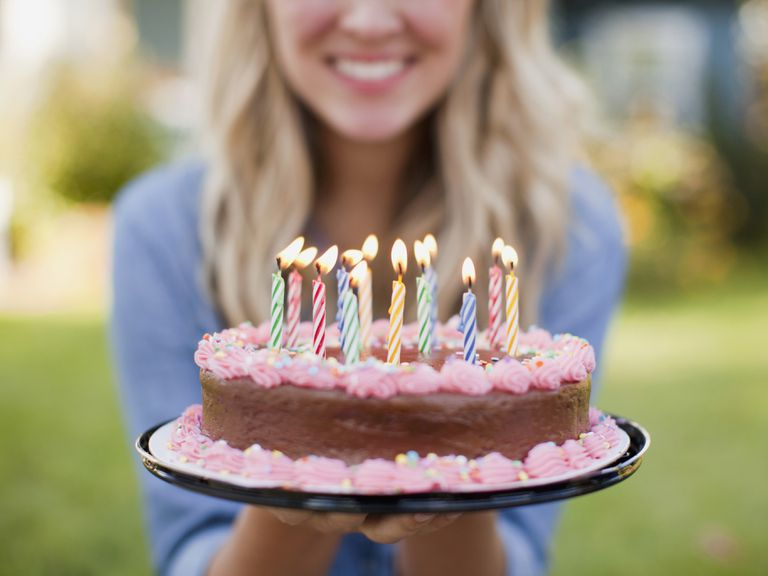 A woman holds a birthday cake with candles