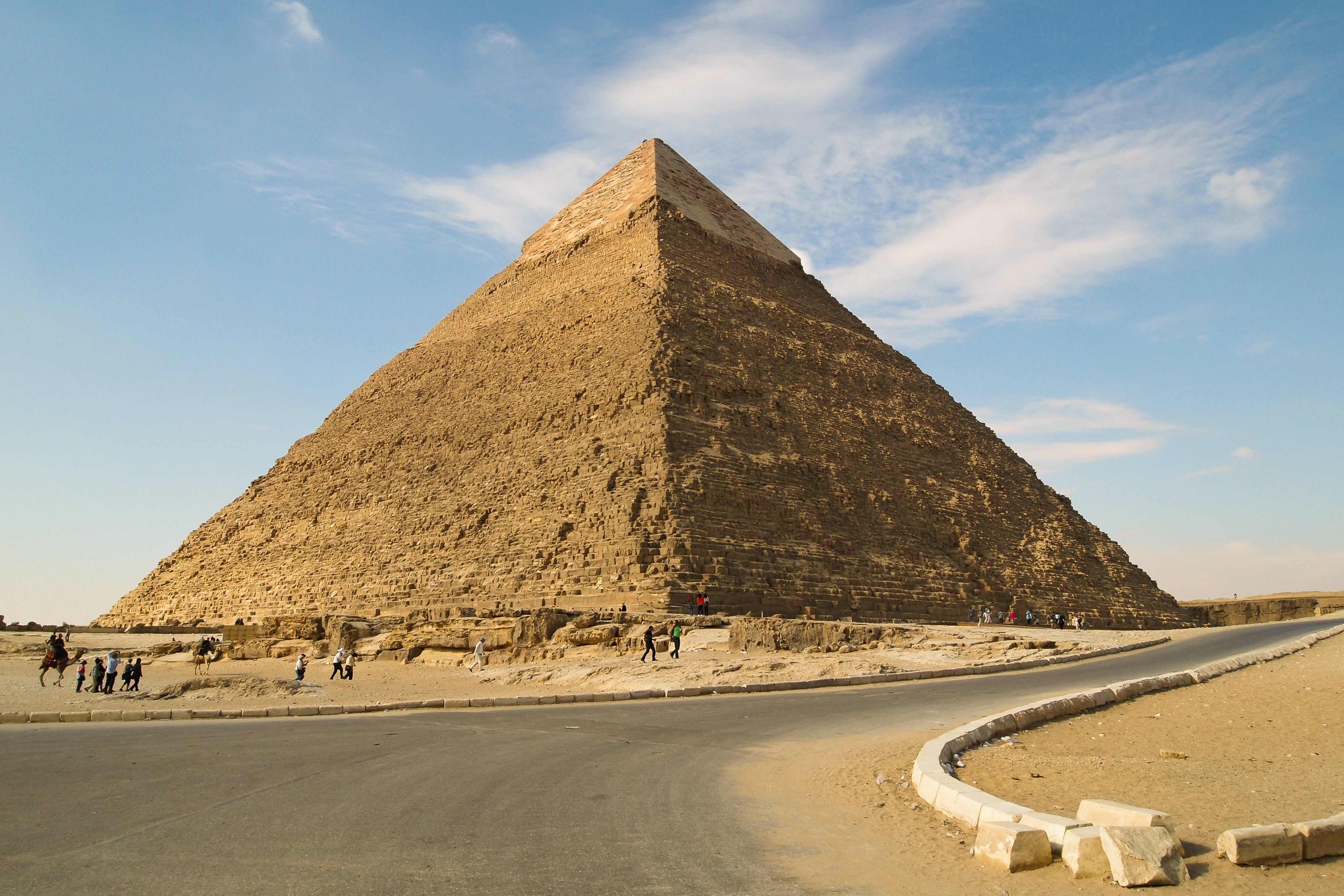 blue sky, large brown pyramid near road and small people and camel figures
