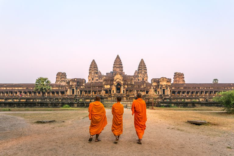 Three buddhist monks walking to Angkor Wat temple, at sunrise. Siem Reap, Cambodia