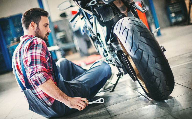 Young man holding tools and sitting on the floor of a repair shop next to a motorcycle