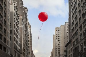 Red balloon floating between buildings
