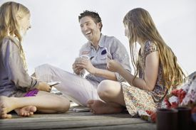 Father playing card game with daughters