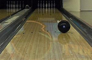 A bowling ball rolling toward the pins.