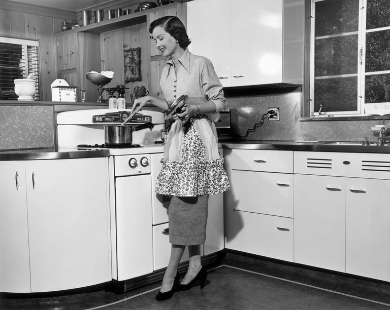 Woman stirring pot at stove, circa 1950s.