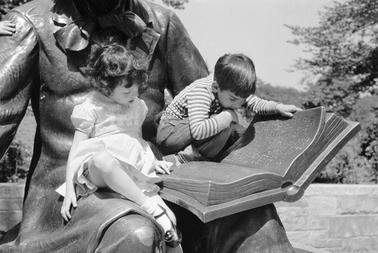 Two Children sitting on a statue of Hans Christian Andersen reading the book, black and white photograph.