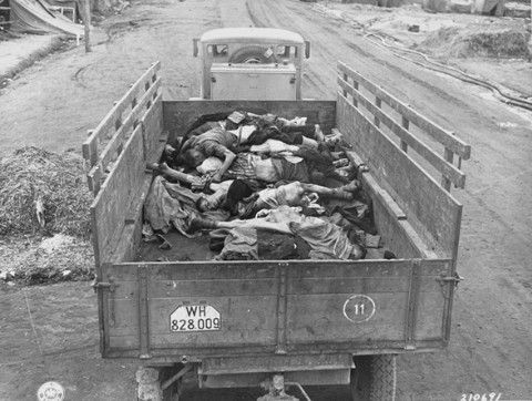 A picture of a British Army truck transporting corpses to mass graves for burial.