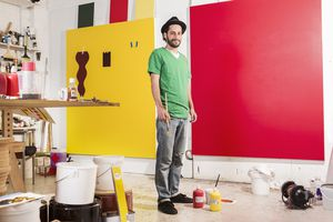 An artist in his studio stands in front two large, colorful canvases