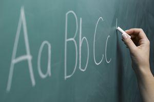 Woman writing alphabet on chalkboard, close-up