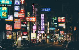A Chinese city at night with many lit up signs.