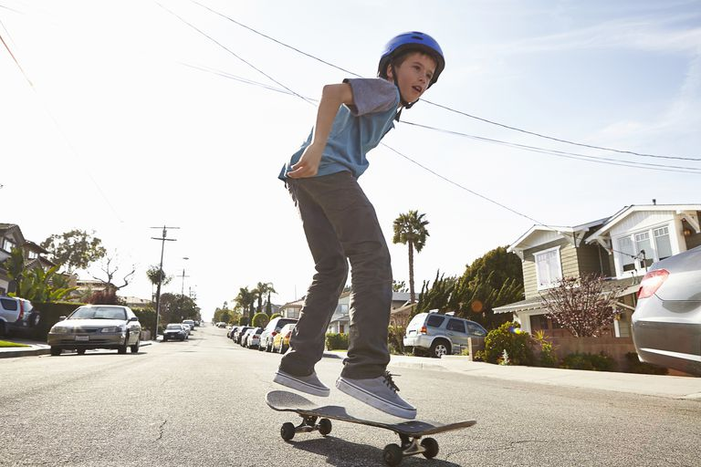 Boy skateboarding on road