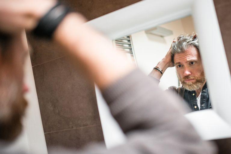 Man looking himself on the mirror