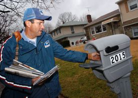A mail carrier delivers envelopes to a mailbox in the suburbs