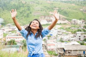 Girl smiling with arms stretched toward the sky