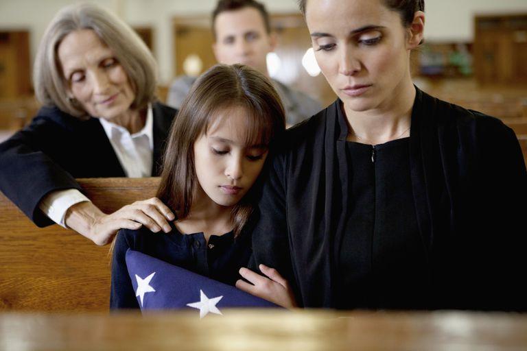 Viuda y su hija siendo consolada.