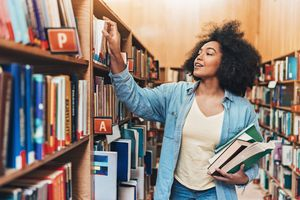 Student holding a stack of books in a library