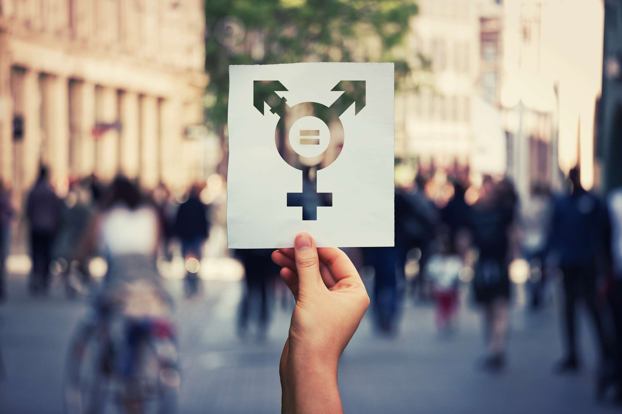 Hand holding a paper sheet with transgender symbol and equal sign inside