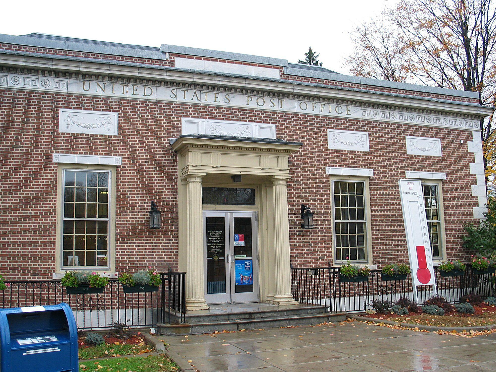 Photograph of ordinary brick postal building, 12-over-12 windows, small classical portico.