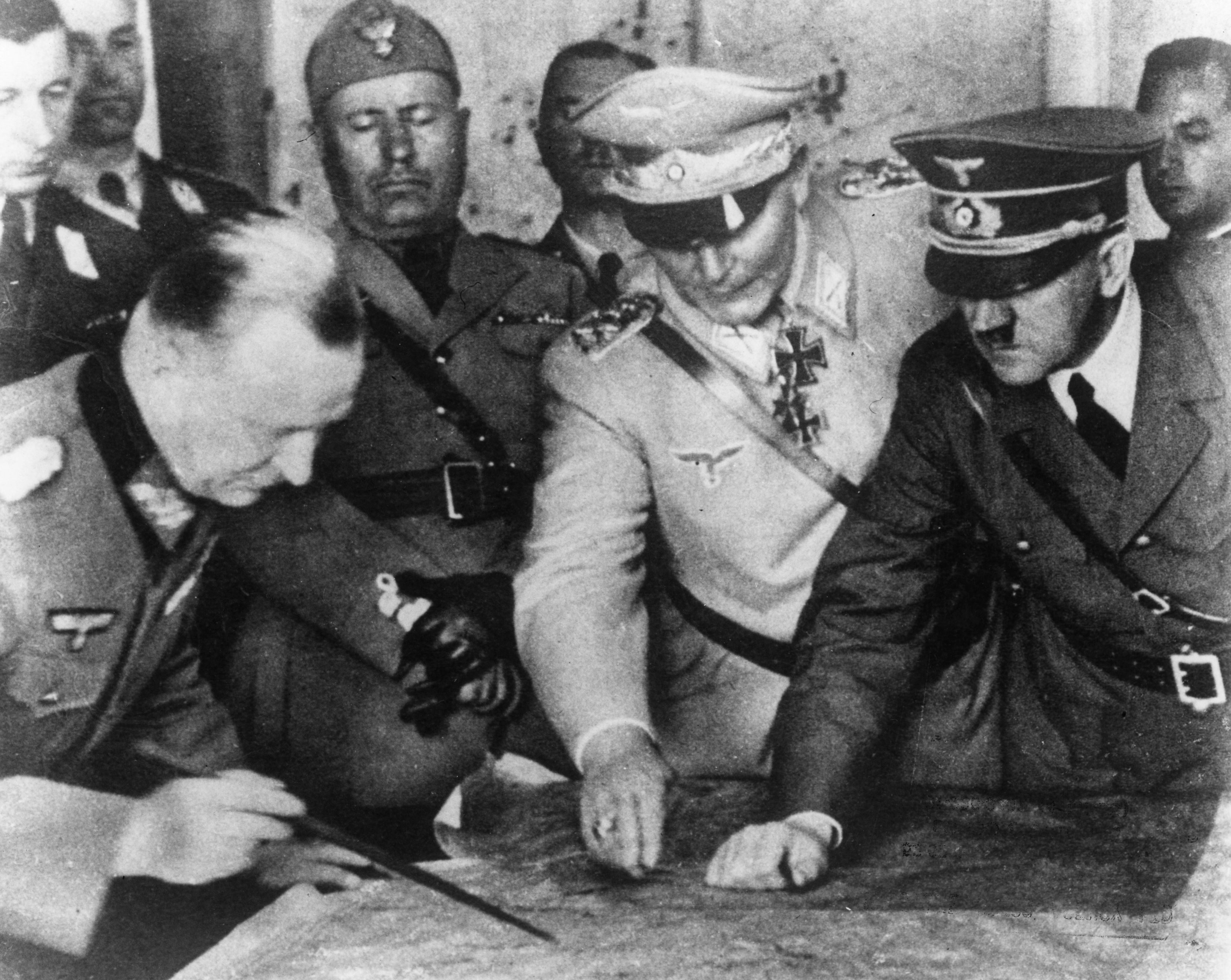 Adolf Hitler (1889 - 1945), Hermann Goering (1893 - 1946) and others plan military strategy at the German Army Headquarters. In the background is Italian dictator Benito Mussolini, circa 1940.