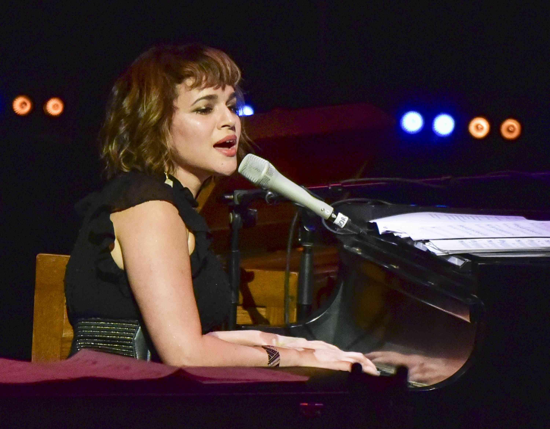 Norah Jones singing at a piano