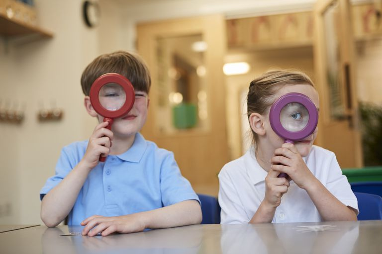 Schoolboy and girl looking through magnifying glasses
