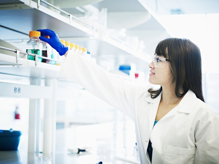 Scientist reaching for bottle of solution in lab