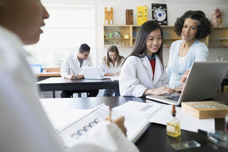 Science teacher helping high school student at laptop