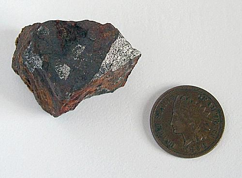 Non-crystallized magnetite next to a coin.