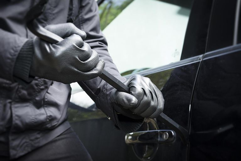 A man breaks into a car with a crowbar