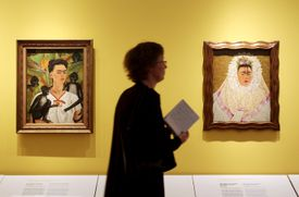 A woman walks past two Frida Kahlo paintings at a museum.