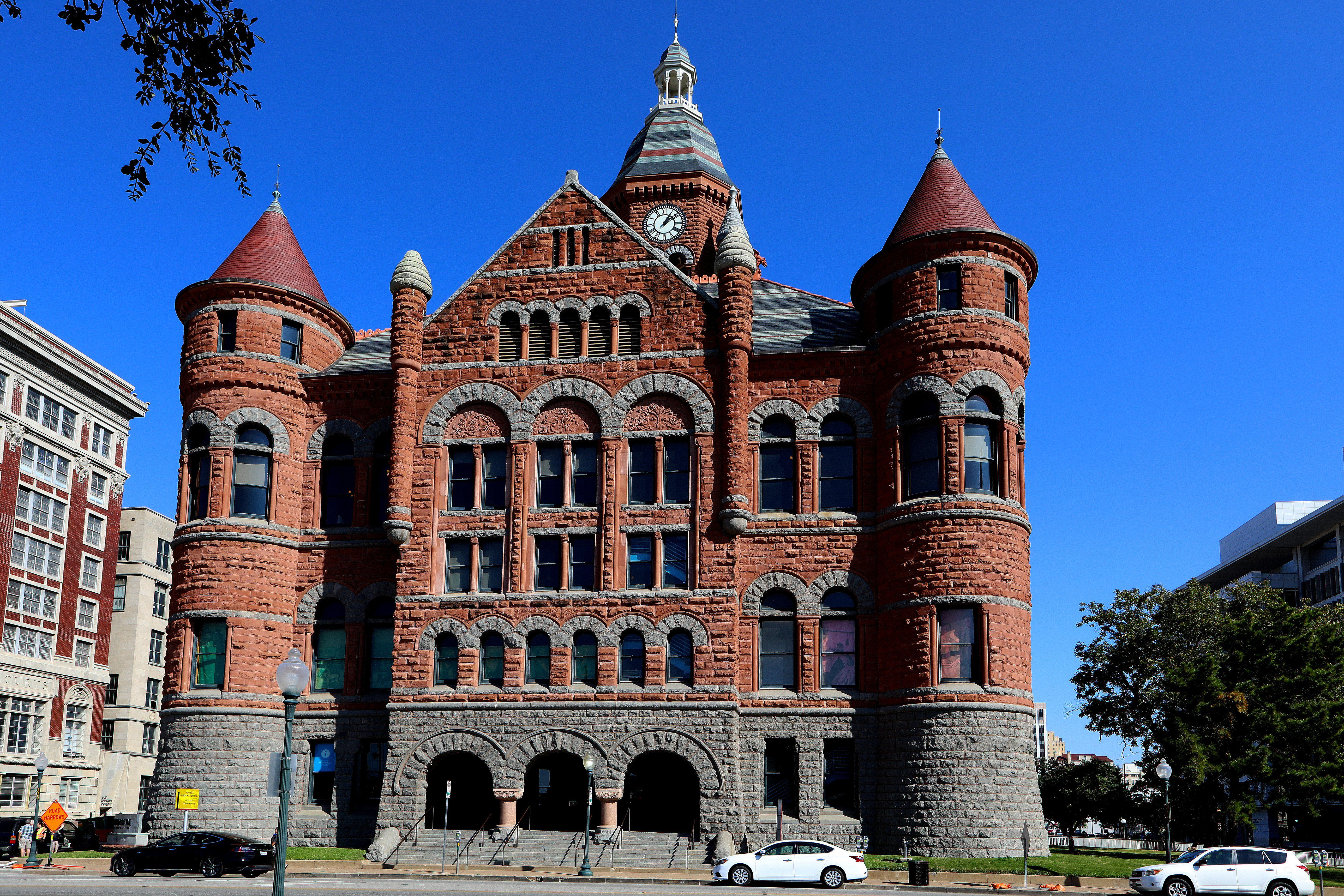 multi-story red stone public building with arched windows and doorways and symmetrical towers