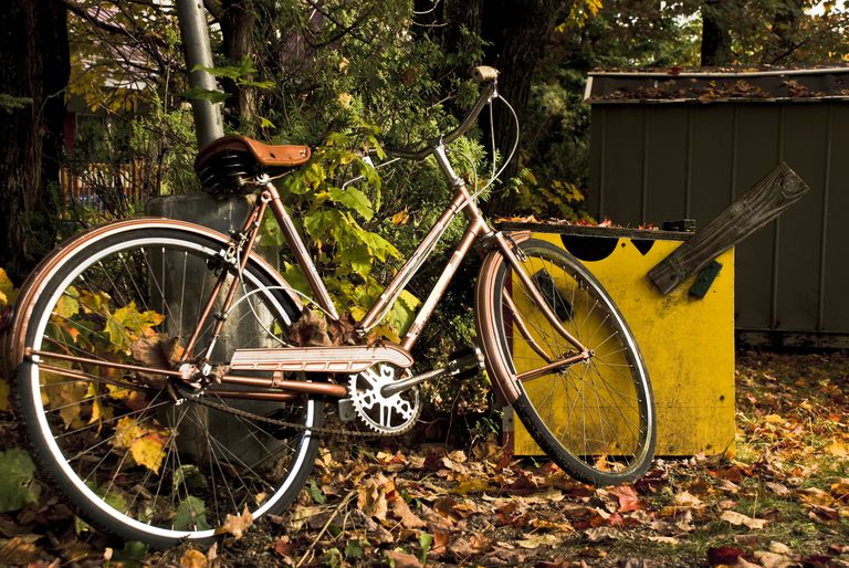 old bicycle in garbage recycling at fall
