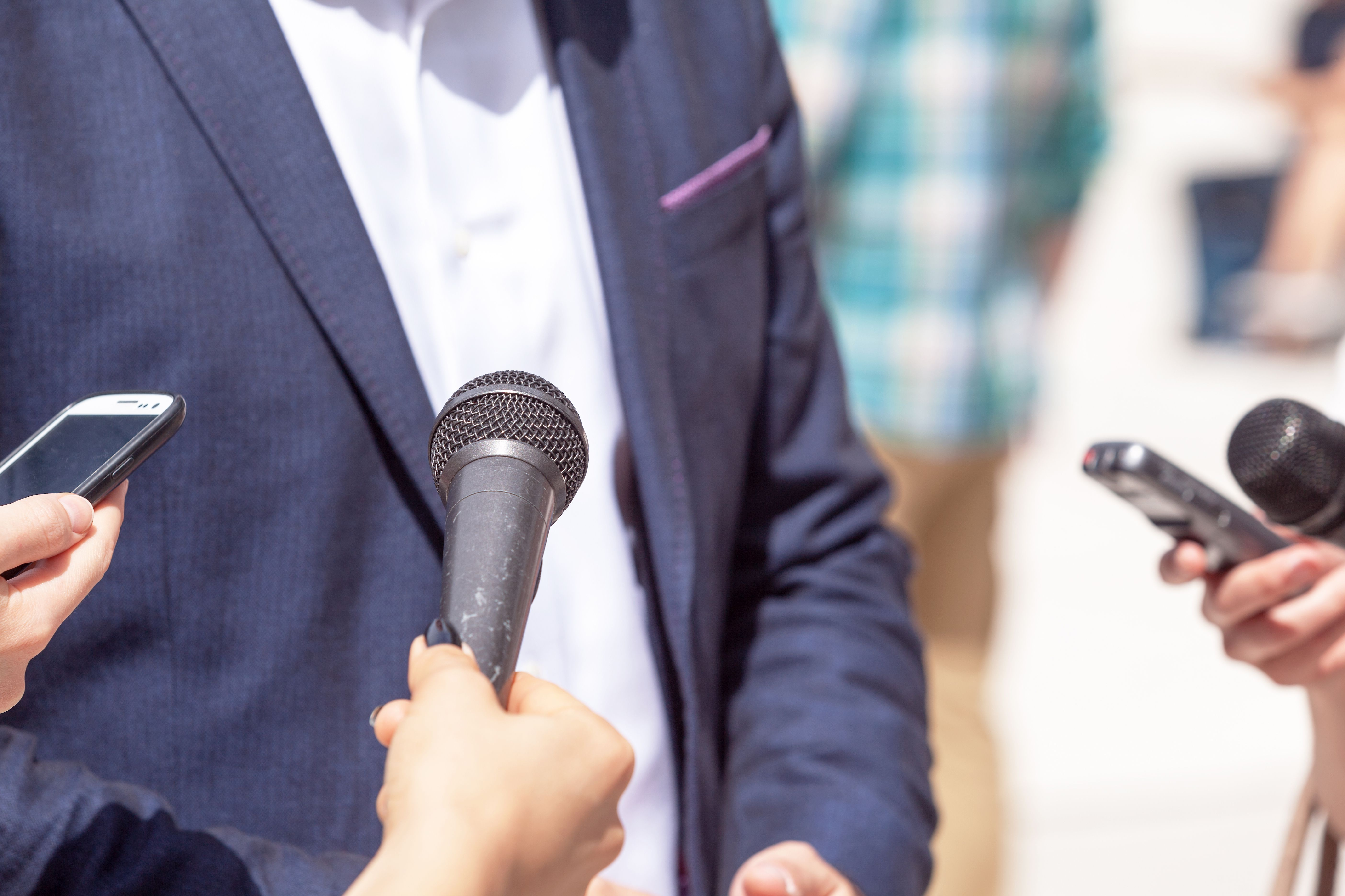 Cropped Image Of Journalist Holding Microphones And Mobile Phone