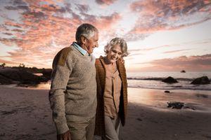 Happy senior couple on beach at sunset