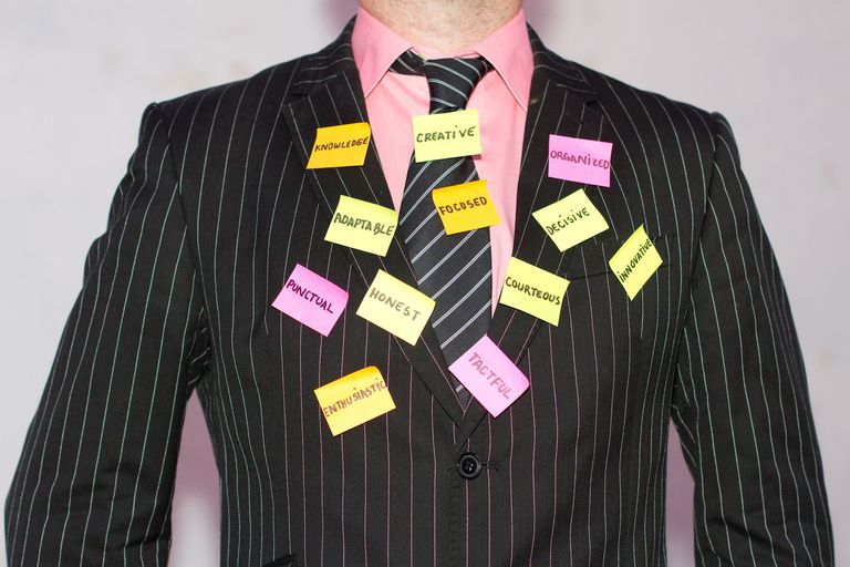 Torso of a man in a pinstriped suit with sticky notes on his suit