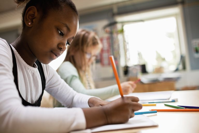 Concentrated girl writing while sitting at desk in classroom