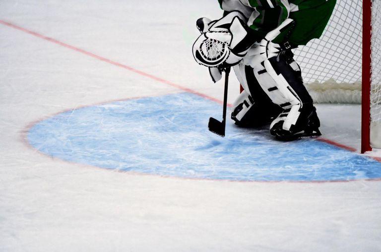 Ice hockey goalie defending goal net.