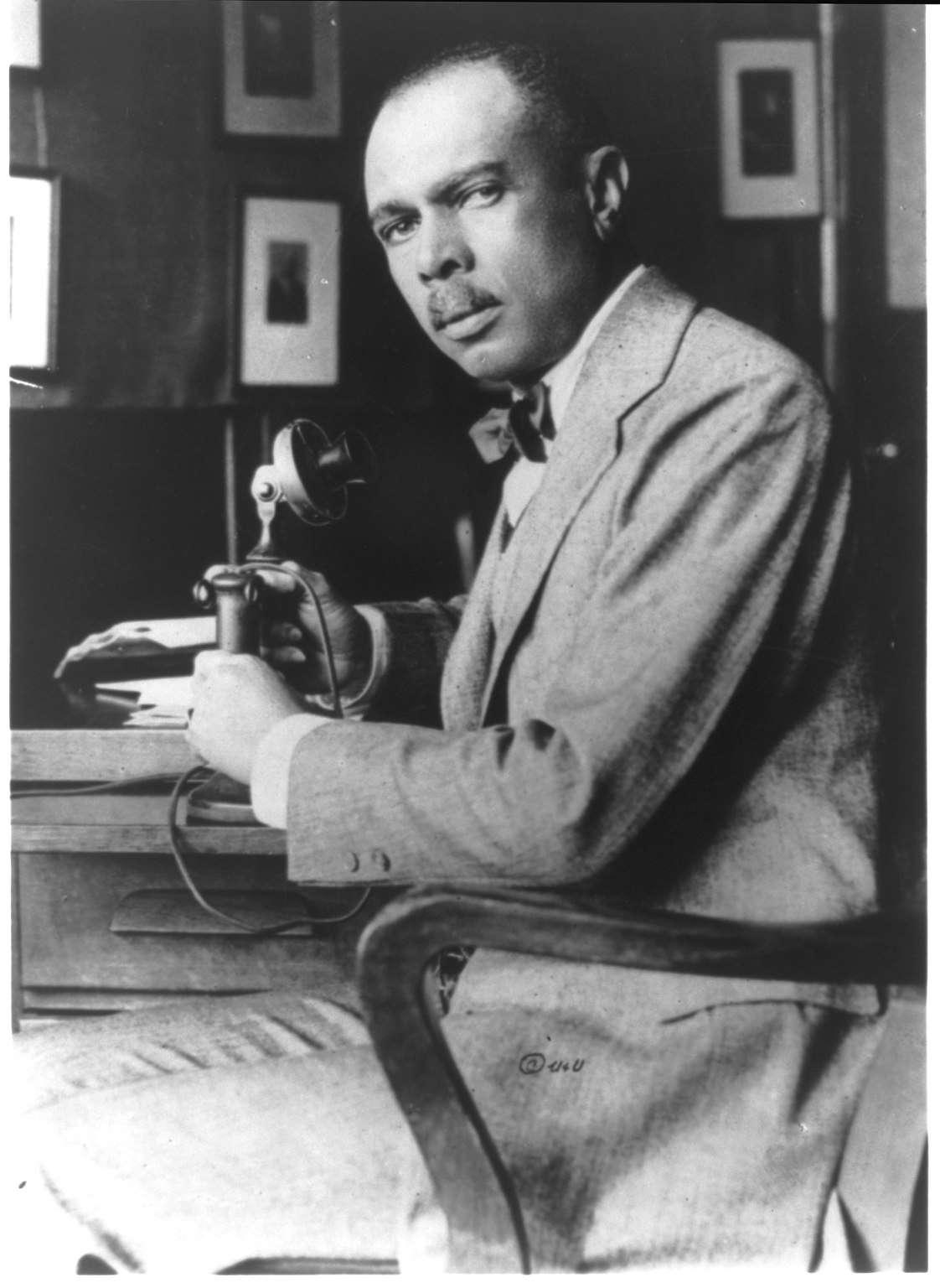 James Weldon Johnson sitting at his desk, black and white photograph.