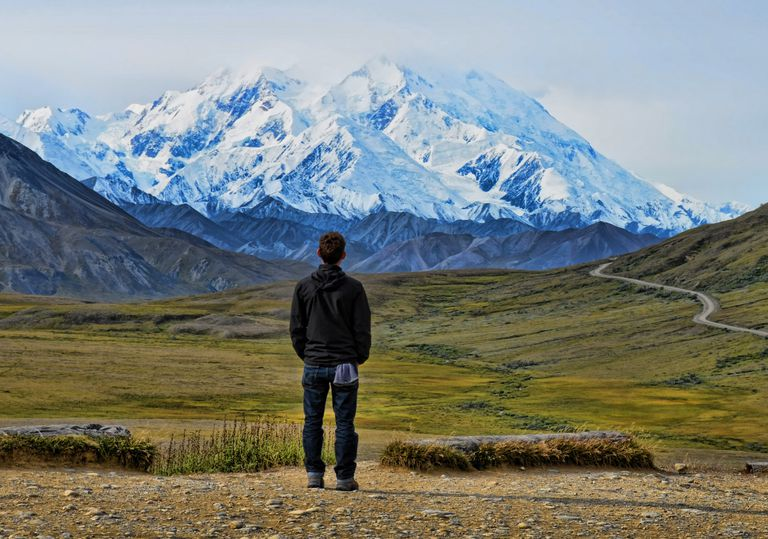 Varón joven contemplando montaña de Alaska.