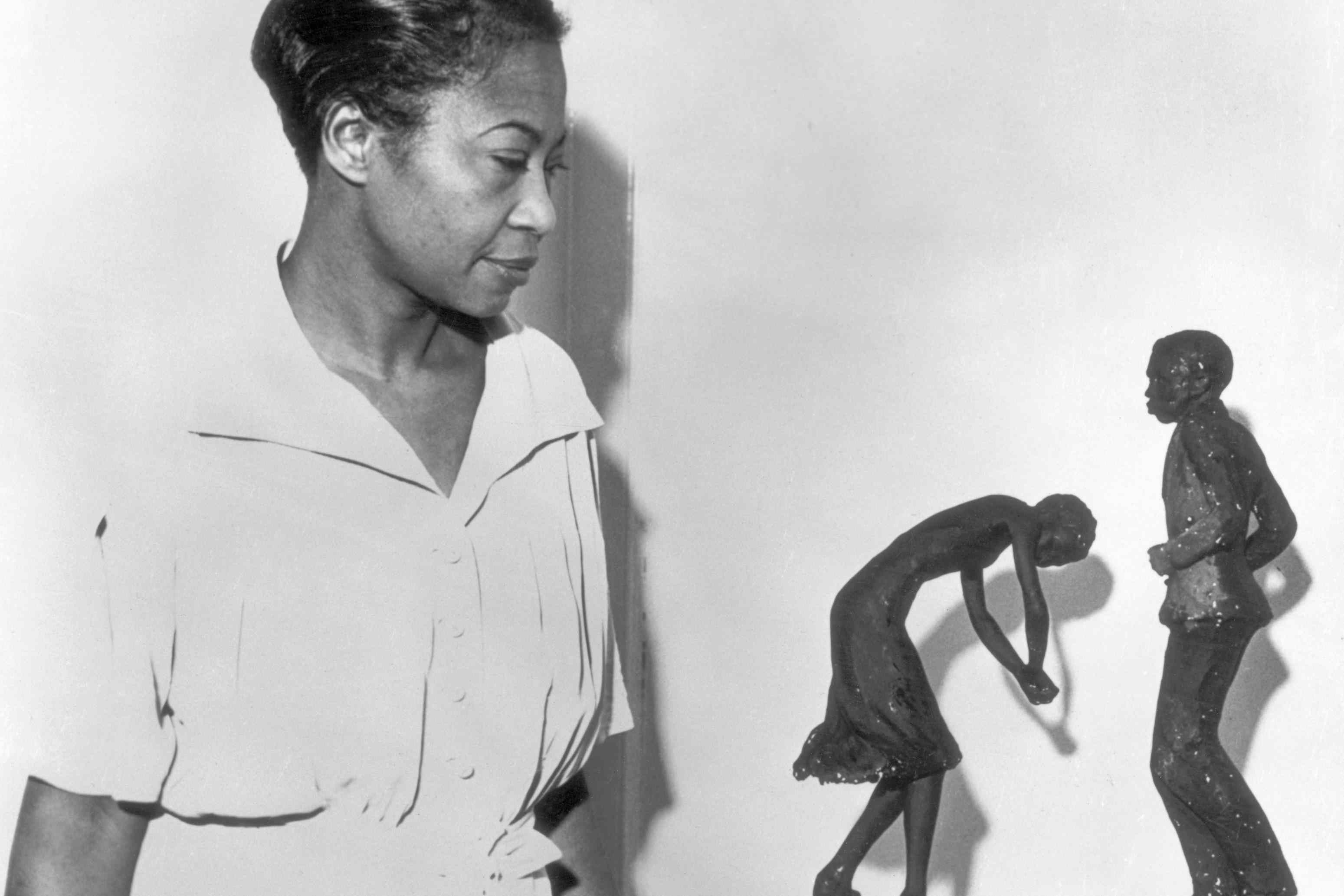 Sculptor Augusta Savage looking at two of her small sculptures