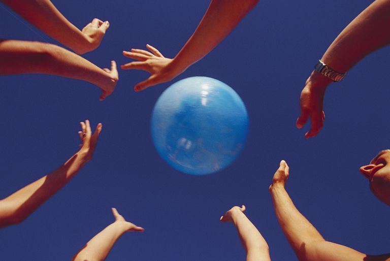 Hands Reaching for Beach Ball