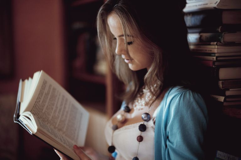 Young girl reading book in library