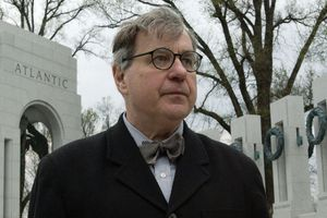 White man, glasses, grey hair, bow tie, Atlantic monument in background, architect Friedrich St.Florian in foreground