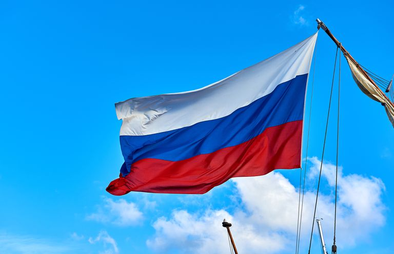Low Angle View Of Russian Flag Against Blue Sky During Sunny Day