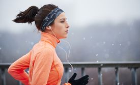 woman running while snowing, listening to music
