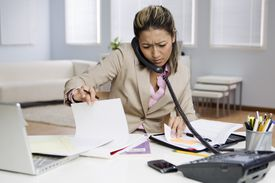 Frowning mixed race businesswoman working at desk