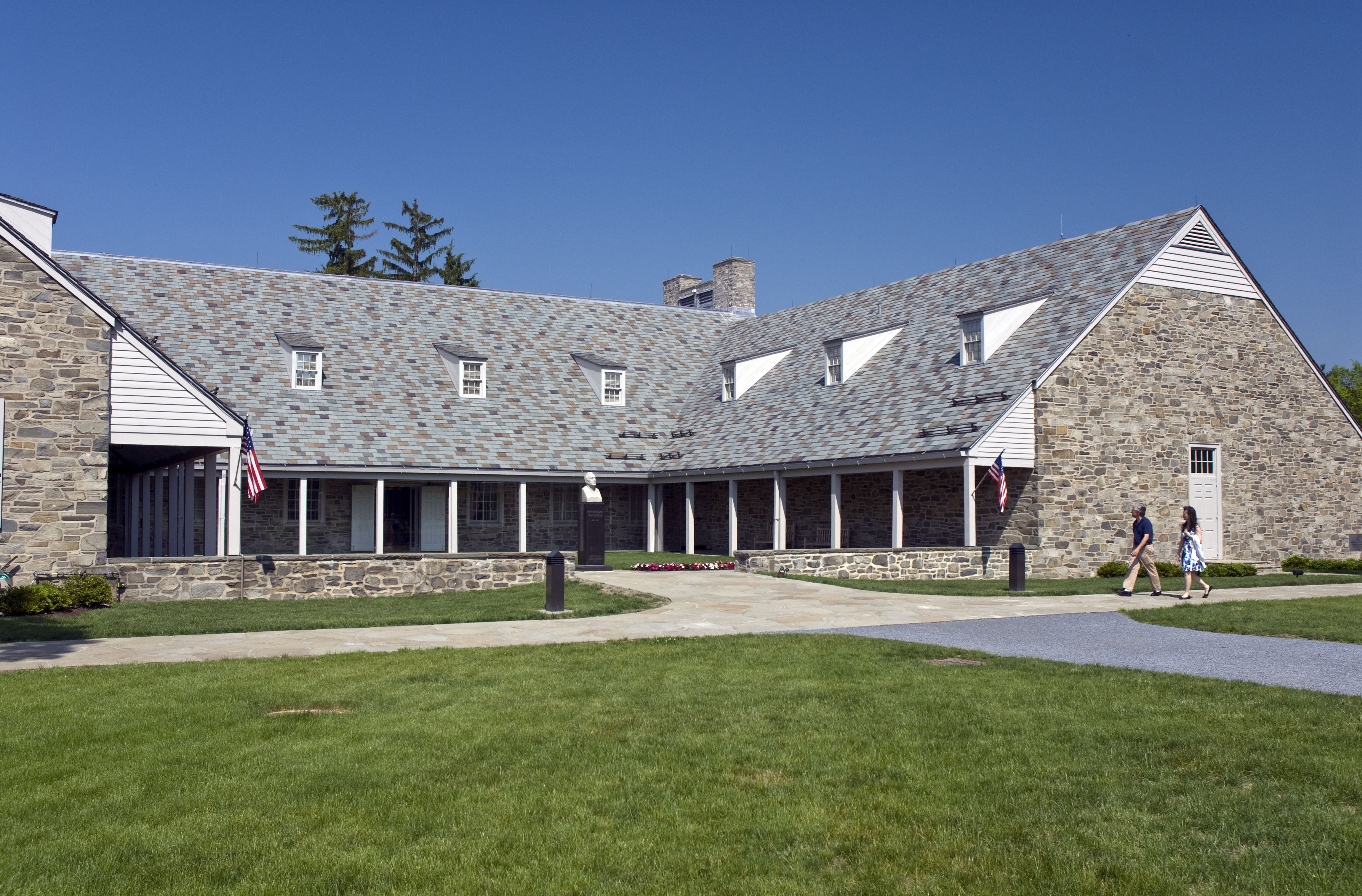 steep grey roof with dormers overhanding a U-shaped building with columned porch