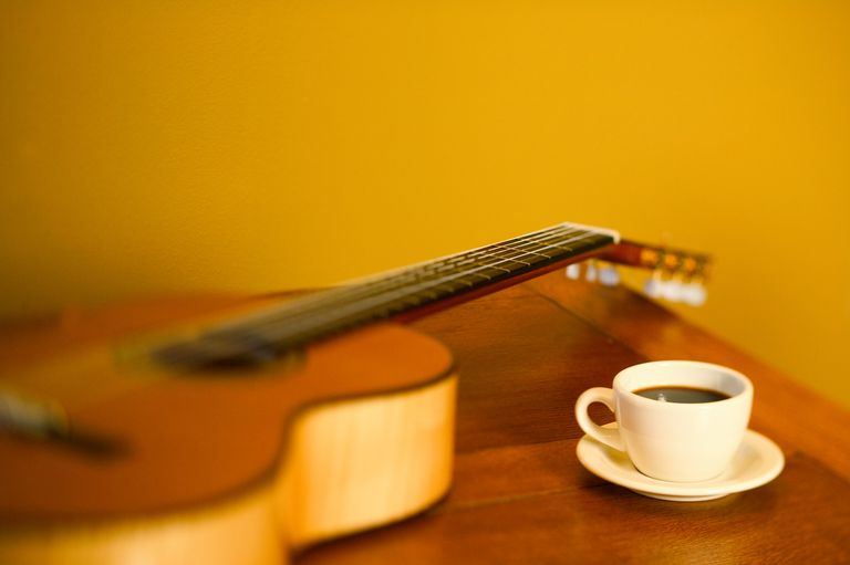 cup of coffee next to a guitar