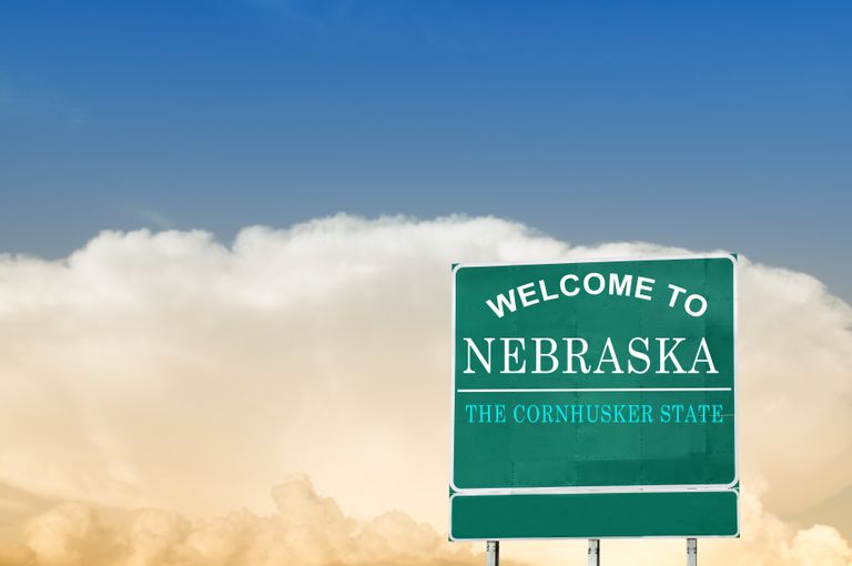 Nebraska state sign under a blue sky.